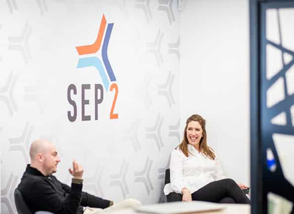 Jake & Natalie chatting in front of the SEP2 logo