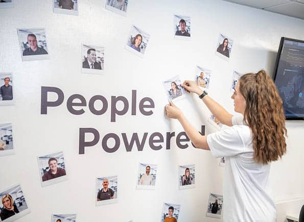 """Payten placing a magnet onto our """"People Powered"""" SEP2 wall"""