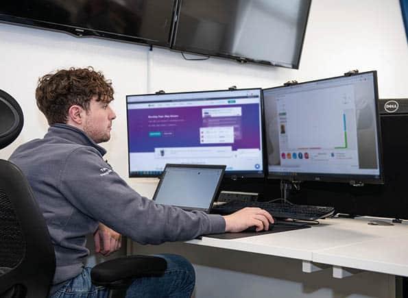 James sitting at his computer looking at 2 screens